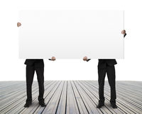 Men holding blank board on wooden floor Royalty Free Stock Image