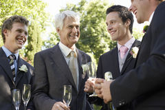 Men Holding Empty Champagne Flutes At Wedding Stock Photography