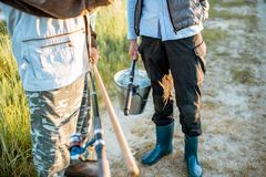 Holding fishing rods and bucket with fish outdoors. Men holding fishing rods and bucket with fresh caught fish outdoors. Close-up view with no face stock image