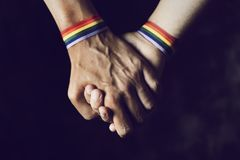 Men holding hands with rainbow-patterned wristband. Closeup of two caucasian men holding hands with a rainbow-patterned wristban on their wrists royalty free stock image