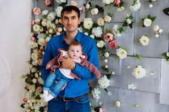 A man is holding his little daughter. Father with a baby in his arms against a wall with flowers. A men is holding his little daughter. Father with a baby in stock photos