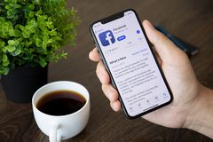 Men holding iPhone X with social networking service Facebook. Alushta, Russia - July 30, 2018: Men holding iPhone X with social networking service Facebook on stock image