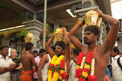 Men Holding Metal Urns on Heads Royalty Free Stock Photos
