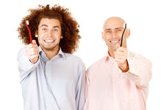 Men holding toothbrushes. Two smiling men holding toothbrushes in extended hands. White background stock image