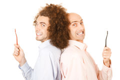 Men holding toothbrushes. Two smiling men holding toothbrushes in extended hands. White background royalty free stock photo