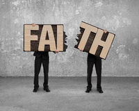Men holding two cracked FAITH word wooden boards. Royalty Free Stock Photos