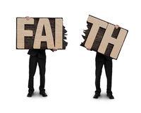 Men holding two cracked FAITH word wooden boards. Royalty Free Stock Photography