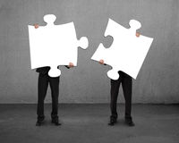 Men holding two puzzles Royalty Free Stock Photos