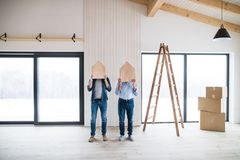 Men holding wooden houses on their heads when furnishing new house, a concept. Two men holding small wooden houses on their heads when furnishing new house, a stock photo