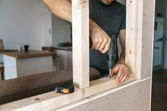 Men in home clothes work with a screwdriver, fixing a wooden frame for a window in their house. Repair yourself.  Royalty Free Stock Photos
