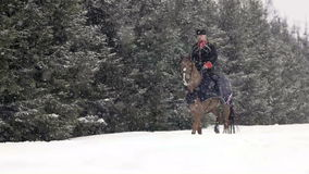 Men horseback riding a big brown horse in beautiful snowy winter landscape. Male rider cantering with large elegant