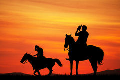 Men on horseback at sunset Royalty Free Stock Image