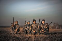 Men hunters group team portrait in rural field posing together against sunrise sky during hunting season. Concept for teamwork royalty free stock photos