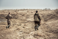 Men hunters running across dry rural field during hunting stock images