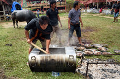 Men impose buffalo meat from cauldron at the funeral ceremony in Tana Toraja Stock Photography