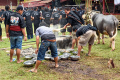 Men impose buffalo meat from cauldron at the funeral ceremony in Royalty Free Stock Photography