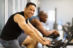 Men indoor biking. Two men doing indoor biking in a fitness club Royalty Free Stock Photos