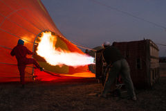 Men inflating hot air balloon before dawn Stock Photos
