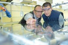 Men inspecting sheet glass in factory. Men inspecting sheet of glass in factory Stock Image