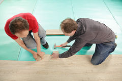 Men installing flooring Royalty Free Stock Photography
