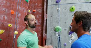 Men interacting with each other during bouldering 4k. Men interacting with each other during bouldering in the fitness studio 4k stock video