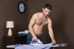 Men ironing. Handsome young man with naked torso ironing his shirt stock photo