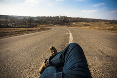 Men in jeans with crossed legs on middle of road. Men in jeans with crossed legs in the middle of road sitting on asphalt Stock Photo