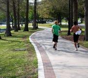 Men jogging. In park stock photo