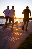 Men jogging at the beach at sunset Stock Photos