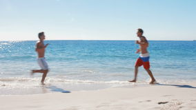 Men jogging on the beach. In ultra hd format stock video