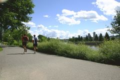 Men jogging in a park. Two man jogging in a park  with the city in background Royalty Free Stock Photography
