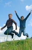 Men jumping against summer landscape stock images