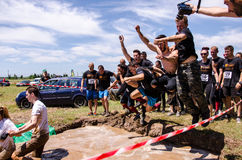 Men jumping in muddy water at Ultimate Mudness, athletic competition in Bucharest Royalty Free Stock Photo