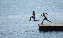 Men jumping in sea off pier. Side view of two people jumping in sea off pier Stock Photos