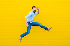 Men jumping on yellow background Stock Photos
