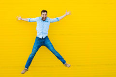 Men jumping on yellow background Stock Images