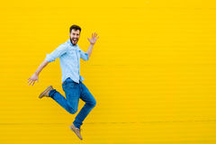 Men jumping on yellow background Royalty Free Stock Photo
