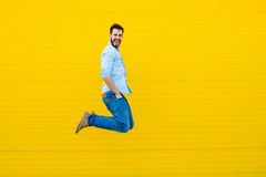 Men jumping on yellow background Stock Image