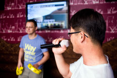 Men at karaoke club. Two men at karaoke club, one singing, the other one playing tambourine Stock Image