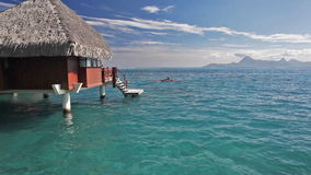 Men on kayaks next to over water bungalow stock video