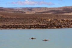 Men on kayaks paddle through the beautiful landscape Royalty Free Stock Photos