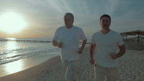 Men keeping fit with regular jogging. Slow motion and steadicam shot of a senior and young men running along the coastline at sunset. Evening jogging on the stock video footage