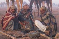 Men Keeping Warm Around An Open Fire Stock Photos