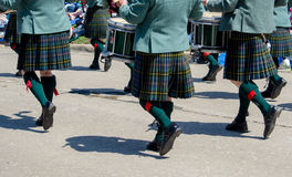 Men in kilts. Men dressed in traditional Scottish kilts, march with their instruments in a parade stock photography