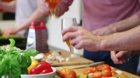 Men In The Kitchen. A group of men are preparing food and drinking beer at home stock footage