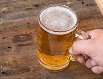 Men& x27 ; la main de s tient une tasse de bière blonde sur les panneaux en bois de vintage foncé photos libres de droits