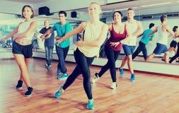 Men and ladies dancing zumba. Happy active men and ladies dancing zumba at lesson royalty free stock images
