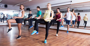 Men and ladies dancing zumba. Happy active young men and ladies dancing zumba at lesson Stock Images