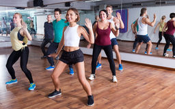 Men and ladies dancing zumba. Happy adult men and ladies dancing zumba at lesson Stock Photography