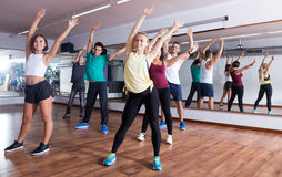 Men and ladies dancing zumba. Happy young men and ladies dancing zumba at lesson Royalty Free Stock Images